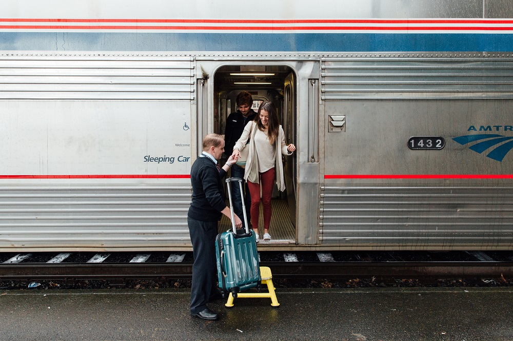 Woman-being-helped-with-luggage-Amtrak