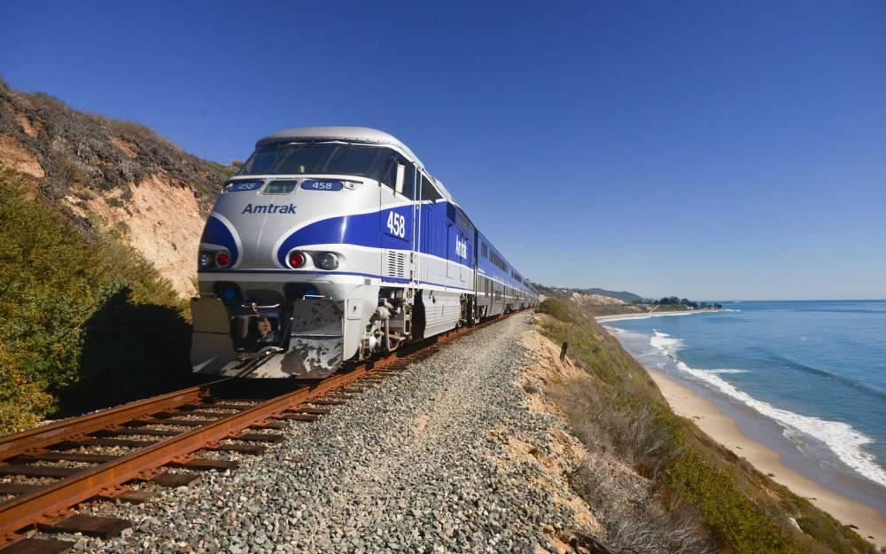Amtrak Surfliner passenger train on tracks running alongside Pacific Ocean beaches near Santa Barbara on the west coast of California, USA